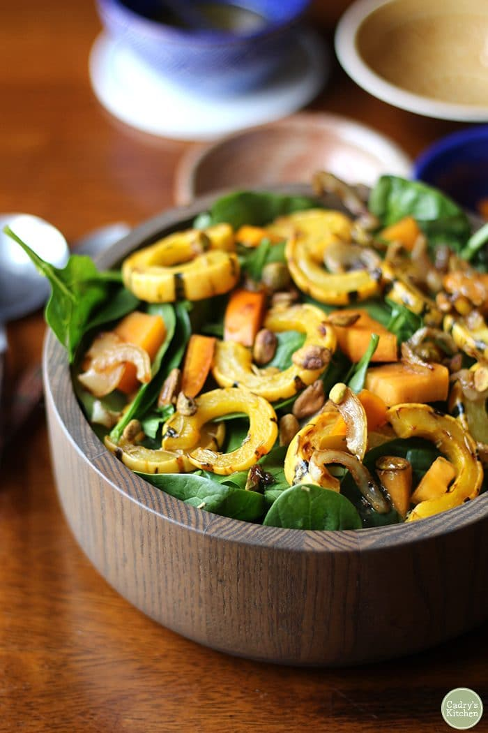 Overhead spinach salad with roasted delicata squash, persimmons, and caramelized onions.