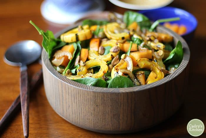 Brown bowl with serving spoons - Spinach salad with delicata squash, persimmons, and caramelized onions.