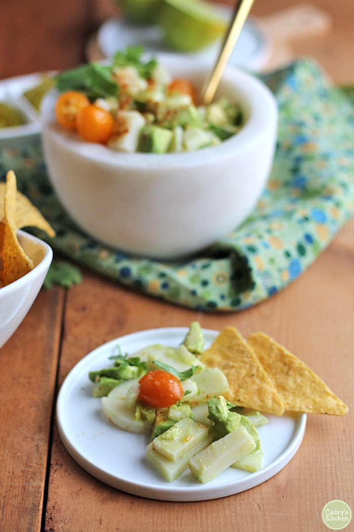 Plate with hearts of palm, tomatoes, and avocado by tortilla chips.