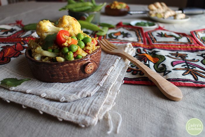 Vegetable fried rice with cauliflower in bowl on table with wooden fork on napkin.