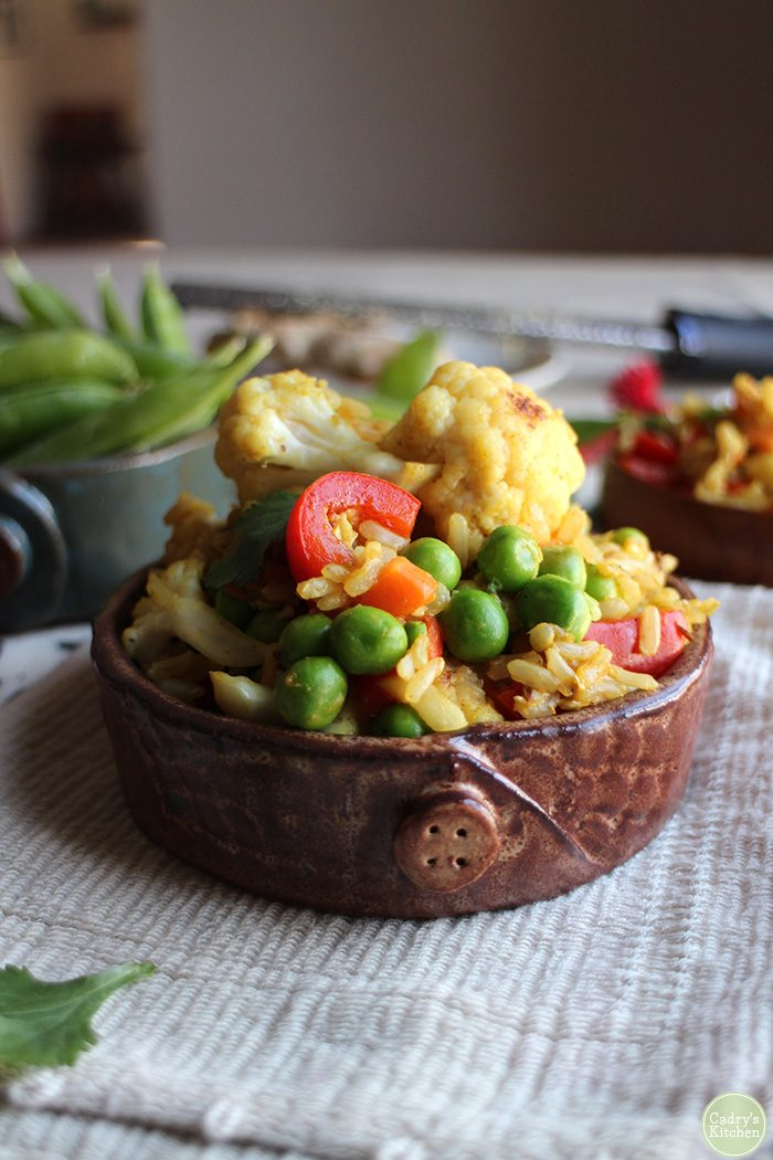 Vegetable fried rice in bowl with peas, cauliflower, and bell pepper.
