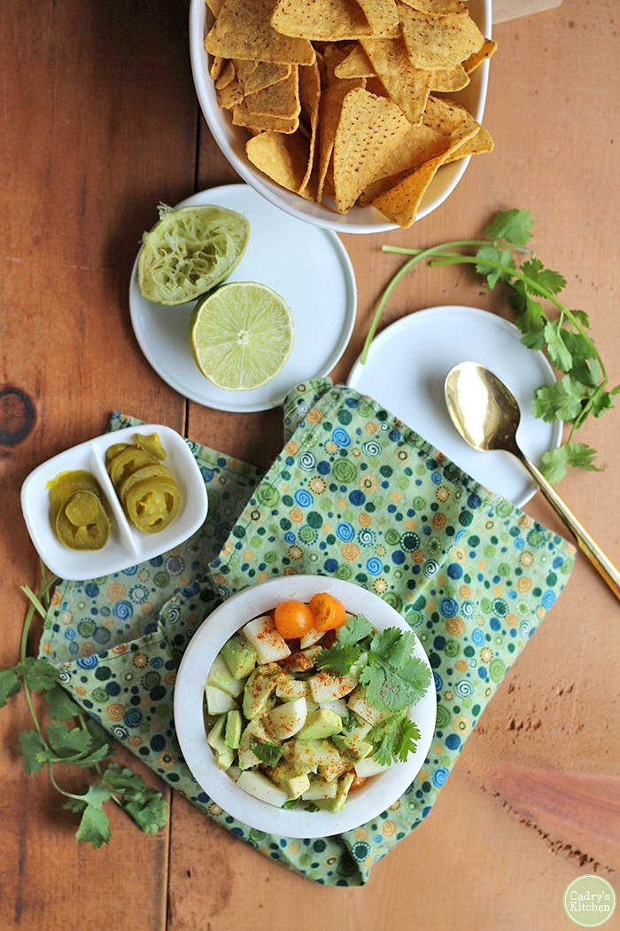 Overhead hearts of palm ceviche on green polkadot napkin with limes and tortilla chips.