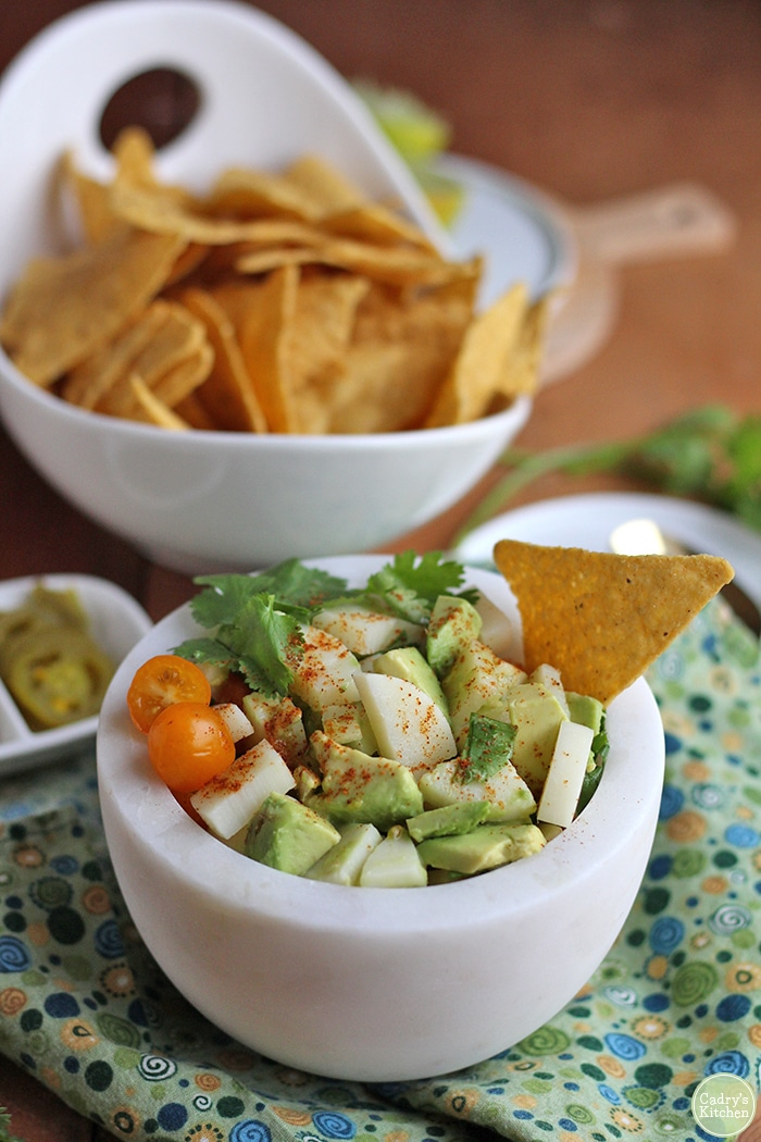 Vegan ceviche in bowl by tortilla chips and jalapenos.