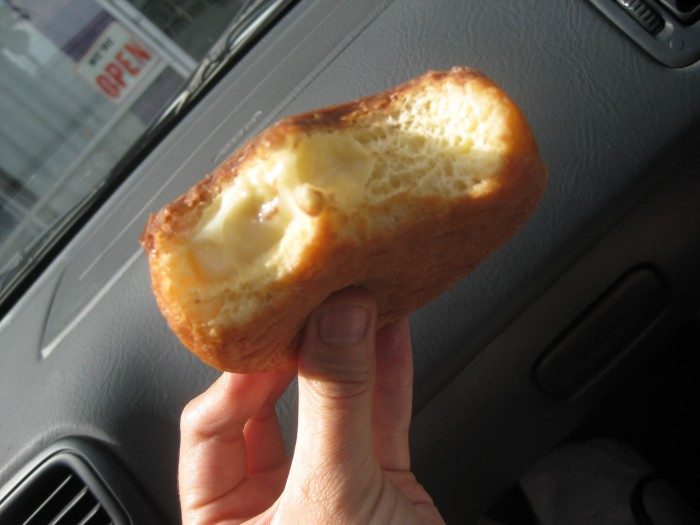 Hand holding soy custard filled donut.