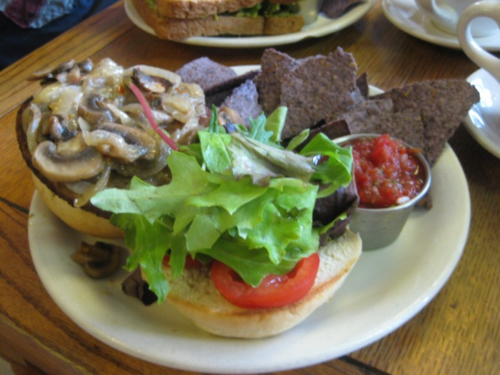 Mushroom burger with chips & salsa on plate.