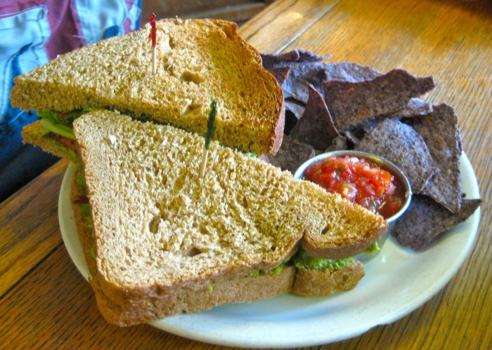 Avocado BLT with chips and salsa on plate.
