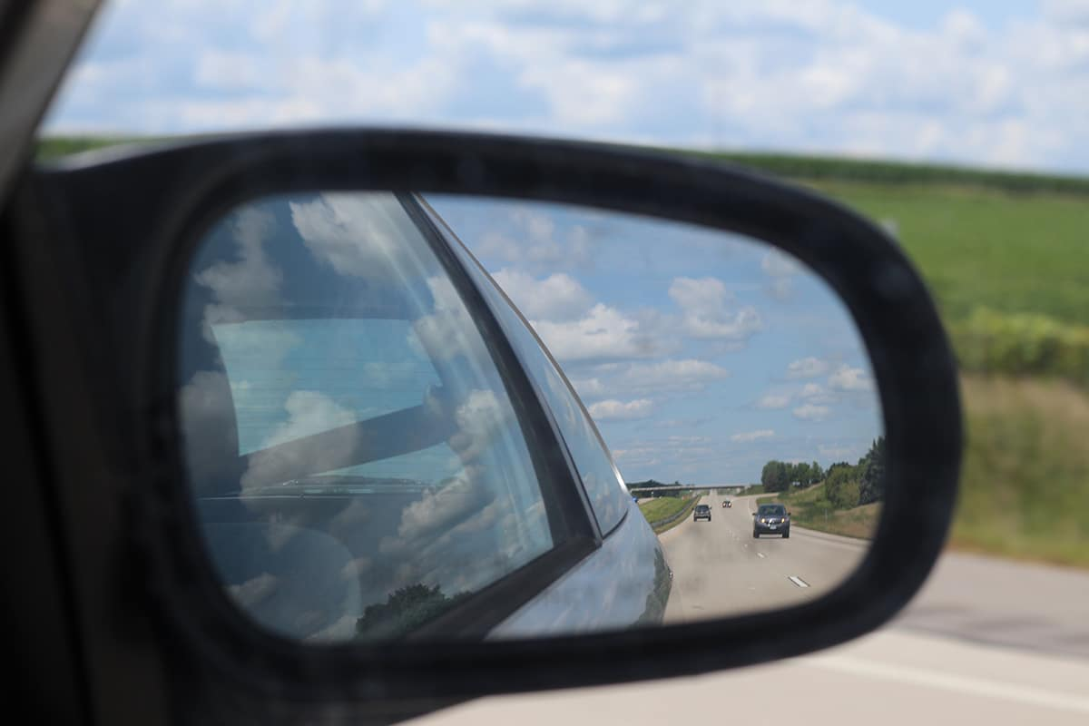 Car in rear view mirror on highway.