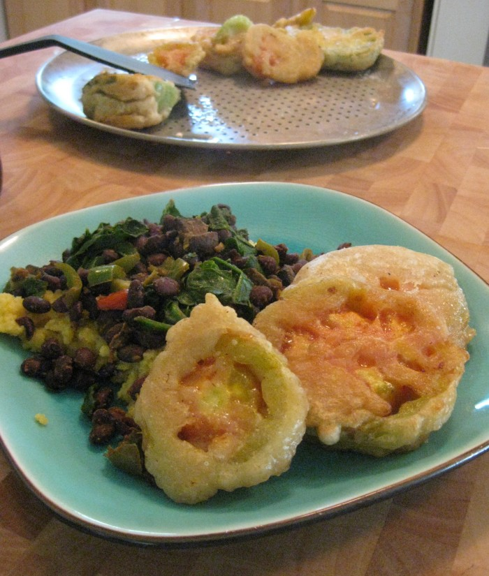 Beer battered fried green tomatoes on plate with black bean hash and polenta.