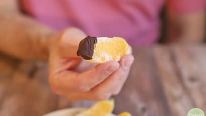 Hand holding orange slice dipped in chocolate.