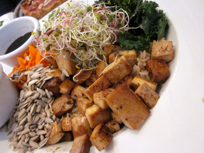Bowl at Flore with tofu, sunflower seeds, sprouts, and kale chips.