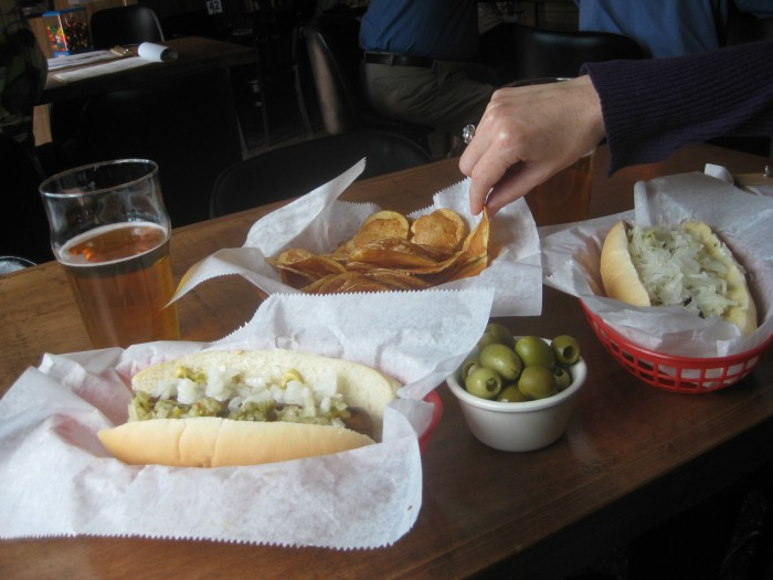 Hand grabbing freshly made chip on table with vegan sausages at Tony's Darts Away in Burbank, California.