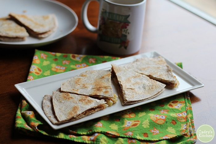 Toasted tortilla wedges filled with PB & banana on plate.