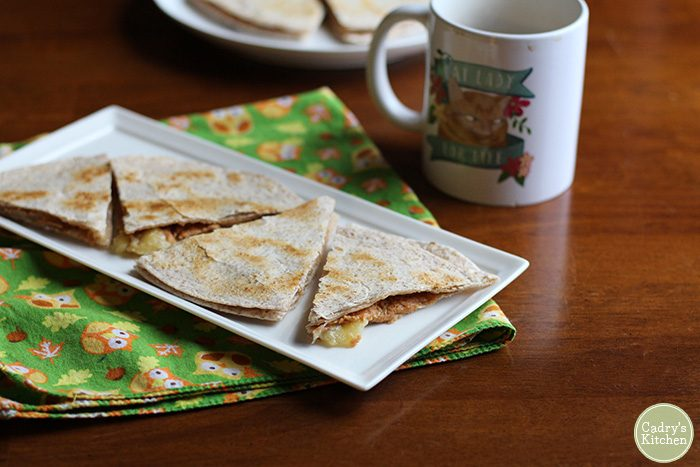 Toasted tortilla wedges with PB & bananas on plate by coffee cup.