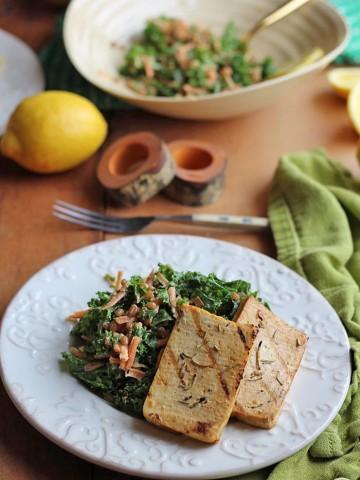 Slabs of tofu on plate with kale salad.