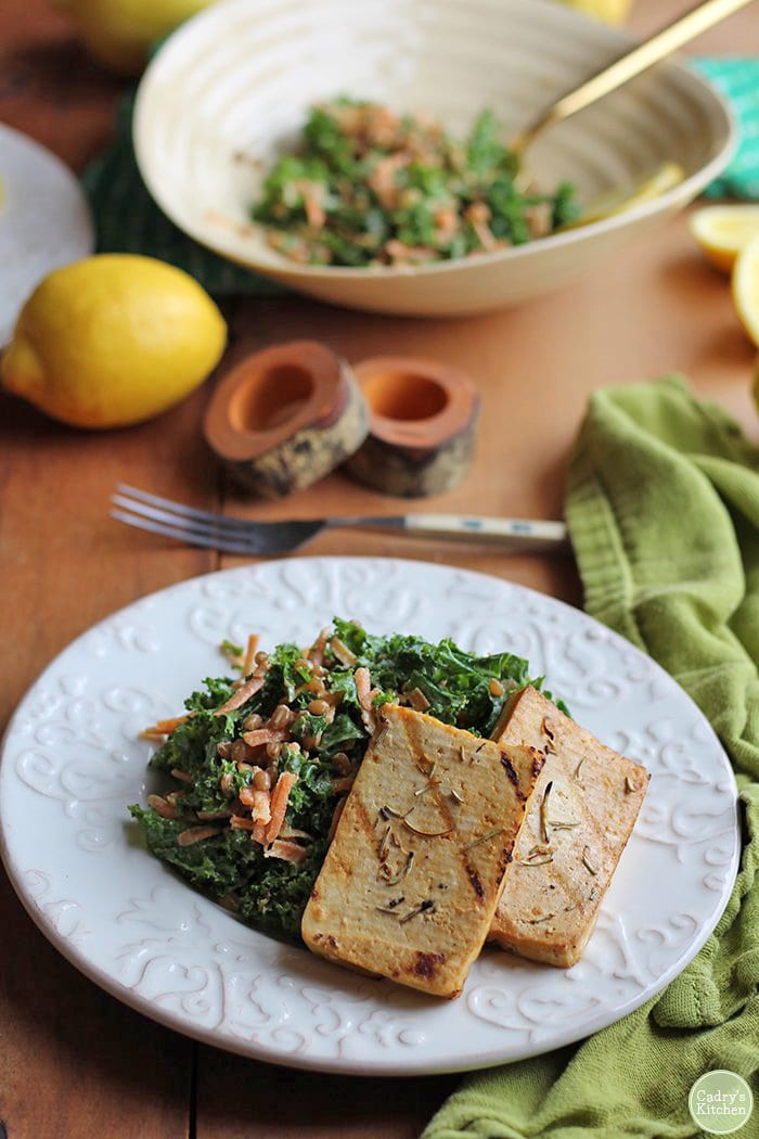 Slabs of tofu on plate with kale salad.