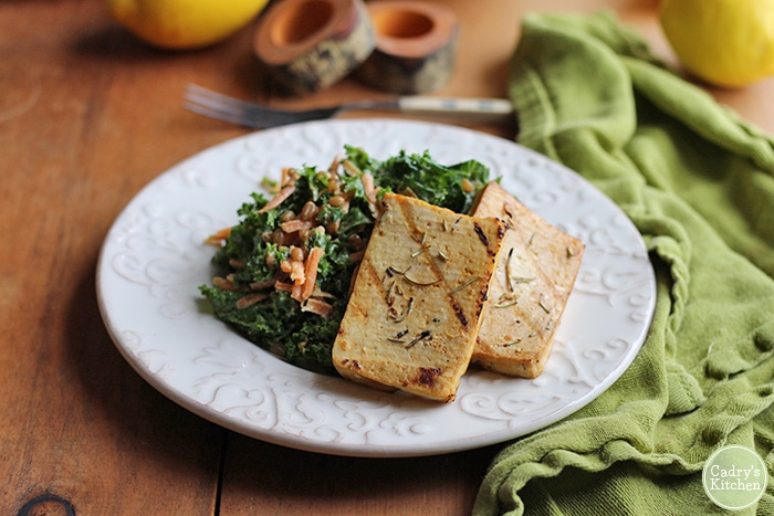 Tofu slabs on plate with kale salad.