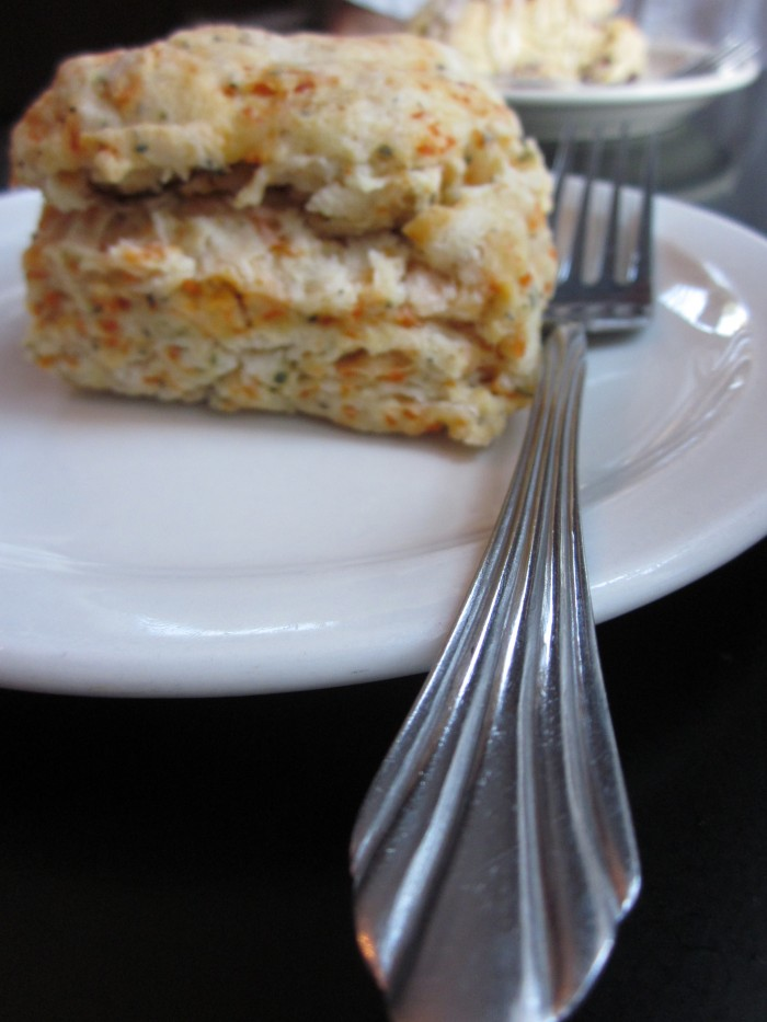 Close-up scone and fork on plate.