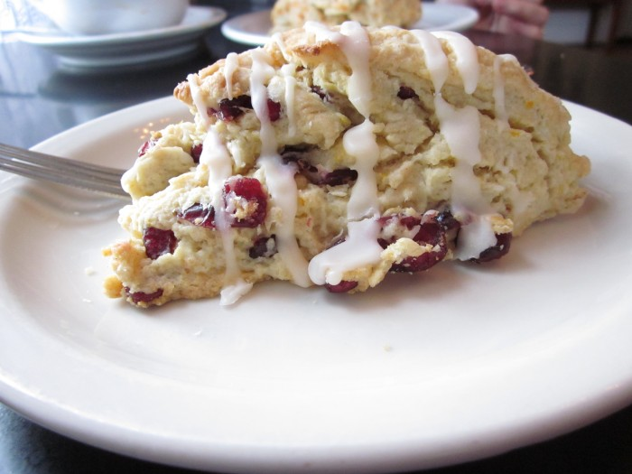 Scone drizzled with icing on plate.
