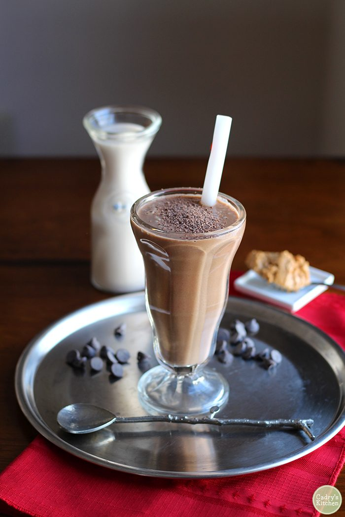 Chocolate peanut butter cup smoothie in tall glass with straw.