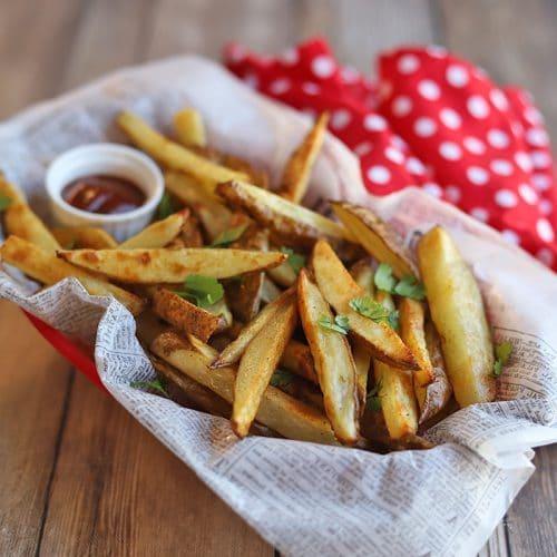 Basket of fries with ketchup and polkadot napkin.
