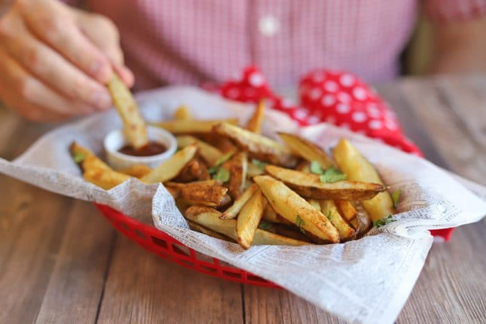 Basket of fries with hand dunking one into ketchup.