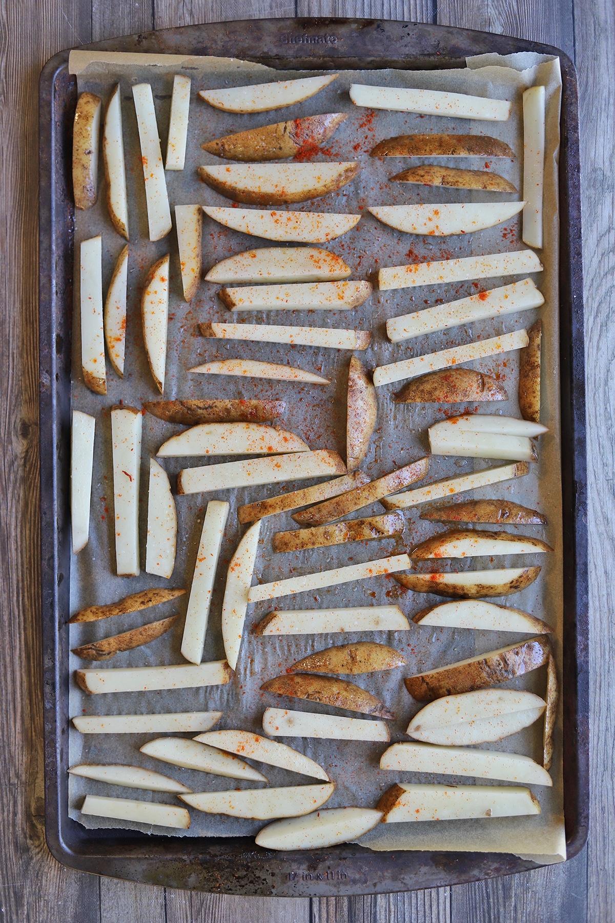 Sticks of potato laying on baking sheet.