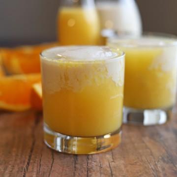 Orange creamsicle drink on table with orange slices.
