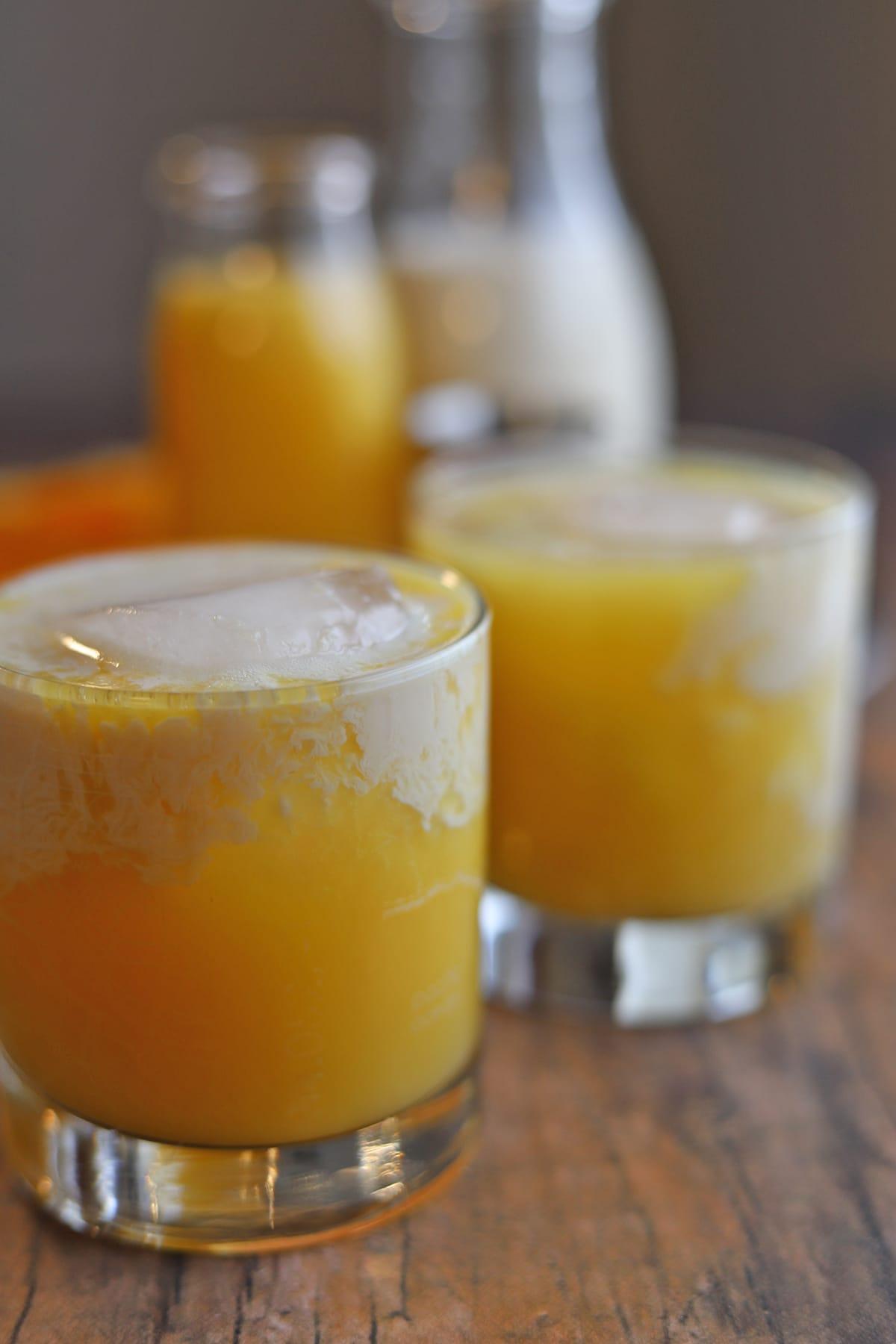 Orange juice cocktail on table with splash of almond milk.