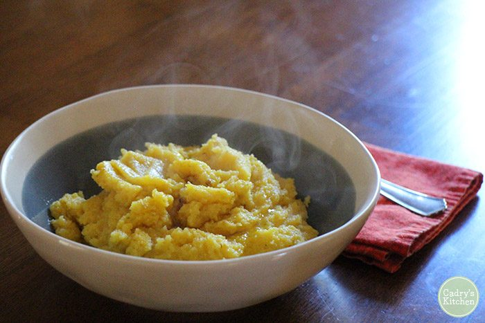 Steaming bowl of polenta on table.