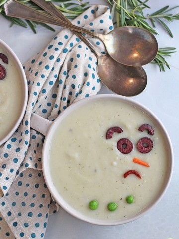 Melted snowman soup in bowl with spoons and napkin.