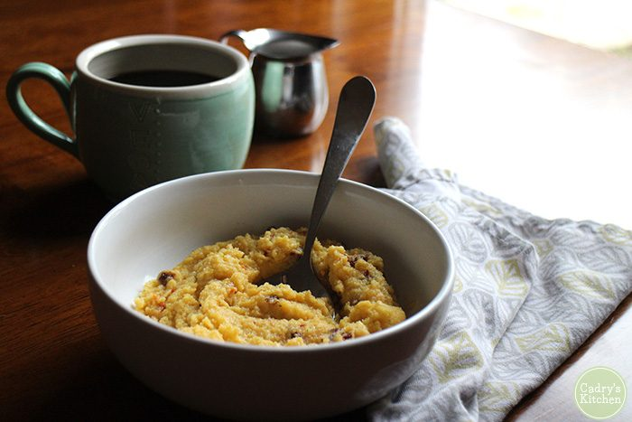 Bowl of creamy vegan polenta with spoon. On the side, a napkin, coffee cup, and creamer pitcher.