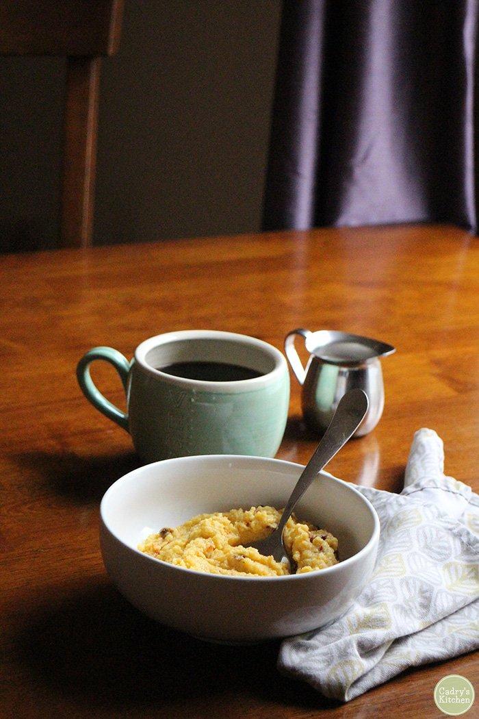Creamy vegan polenta in bowl with coffee & vegan creamer.