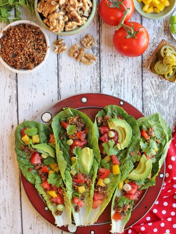 Platter of romaine leaves with walnut meat, avocado, and vegetables.