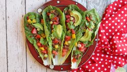 Overhead raw vegan tacos with walnut taco meat, avocado, tomatoes, and bell pepper on plate.