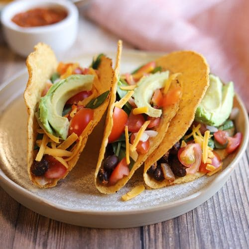 Black bean tacos on plate by napkin.