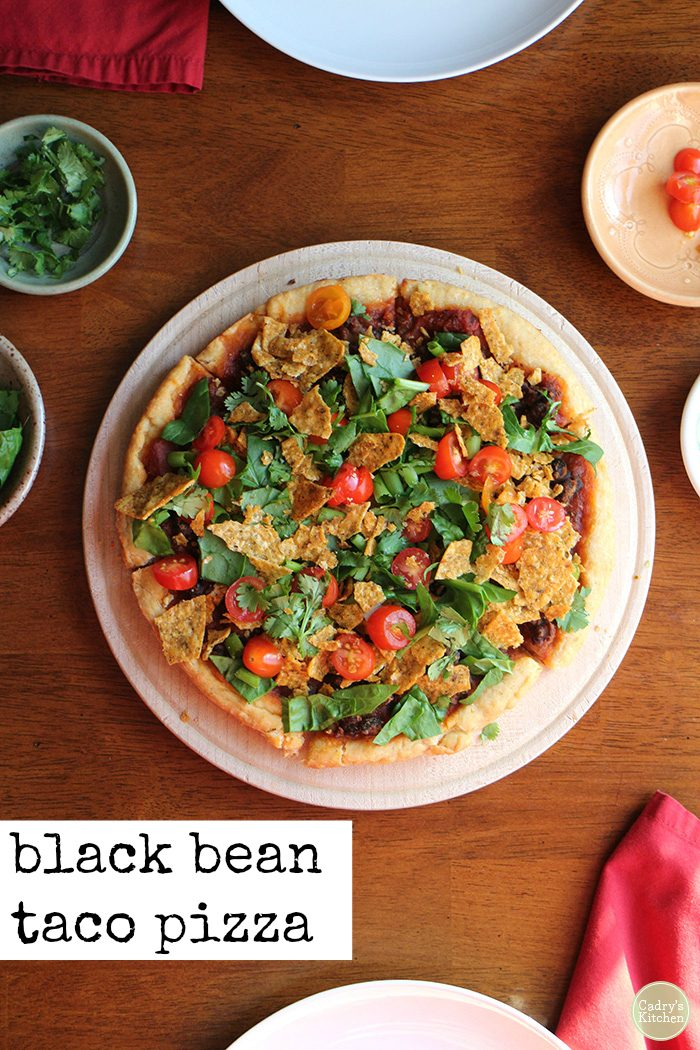 Text: Black bean taco pizza. Overhead vegan taco pizza with beans, chips, tomatoes, and lettuce on cutting board.