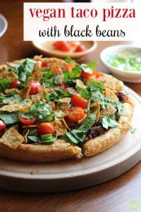 Text: Vegan taco pizza with black beans. Close-up vegan taco pizza with lettuce, tomatoes, and chips.