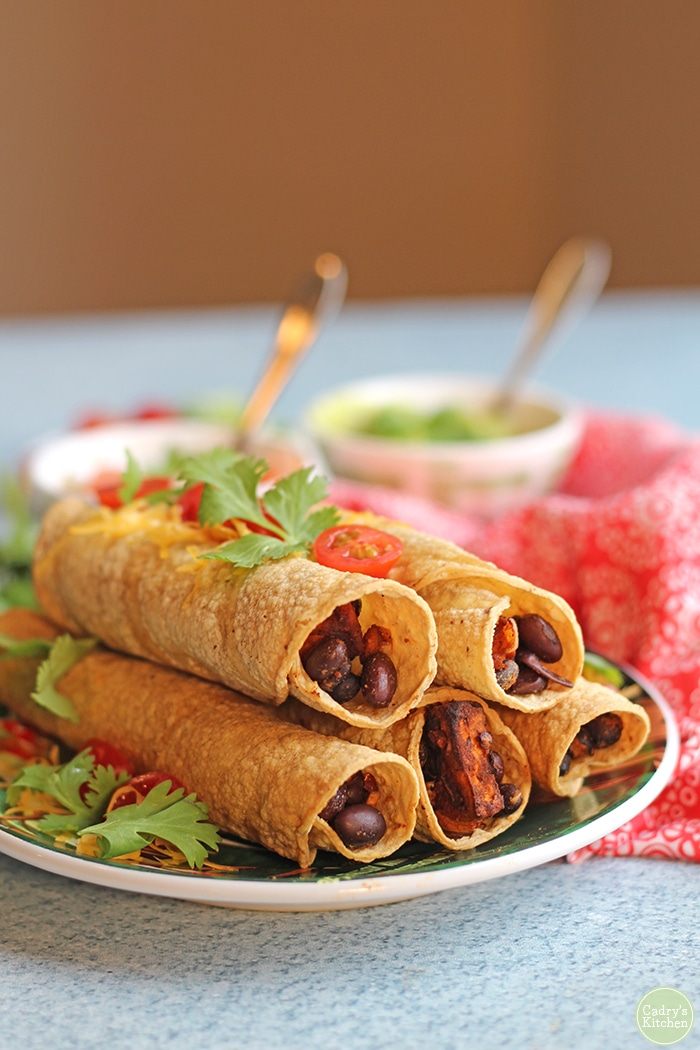 Baked taquitos on plate with cilantro and cherry tomatoes. Filled with sweet potatoes & black beans.