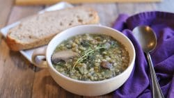 Double lentil mushroom barley soup in bowl by bread.