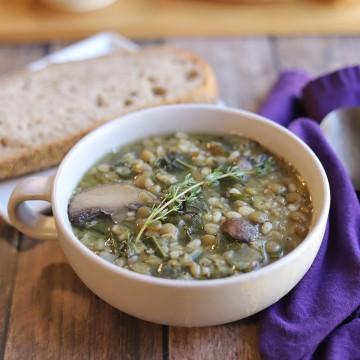 Double lentil mushroom barley soup in bowl by bread.