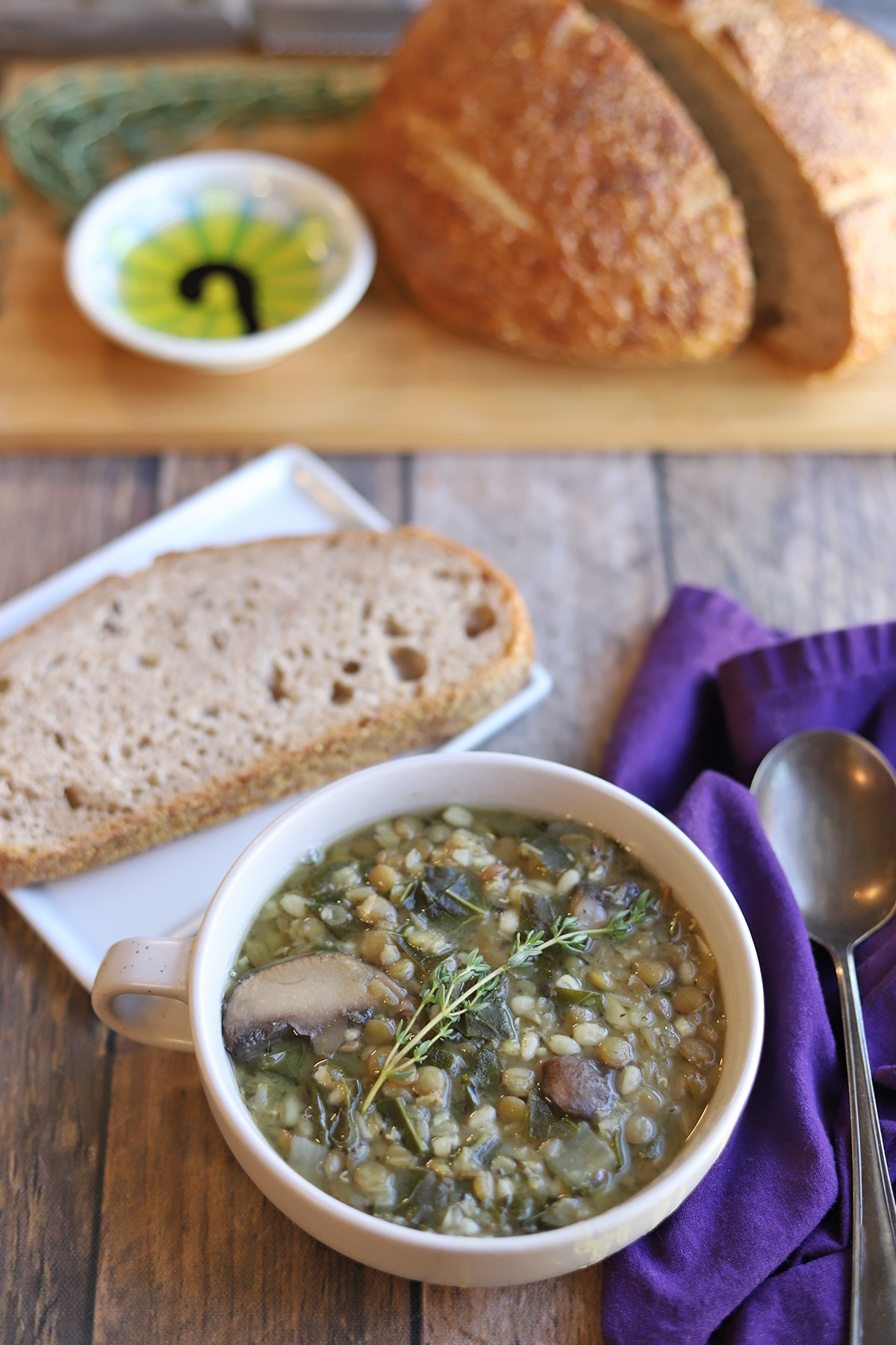 Lentil mushroom barley soup in bowl on table with bread and oil.