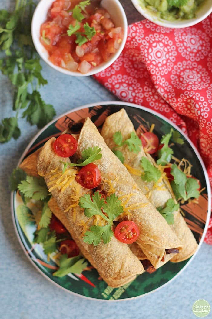 Overhead baked taquitos on plate & topped with cilantro, non-dairy cheese, and cherry tomatoes.