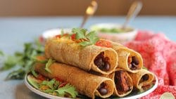 Baked taquitos stuffed with sweet potatoes & black beans on plate and topped with cilantro.