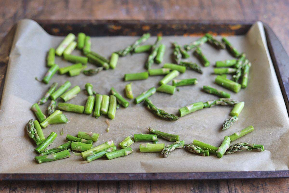 Chopped asparagus on a baking sheet with parchment paper.