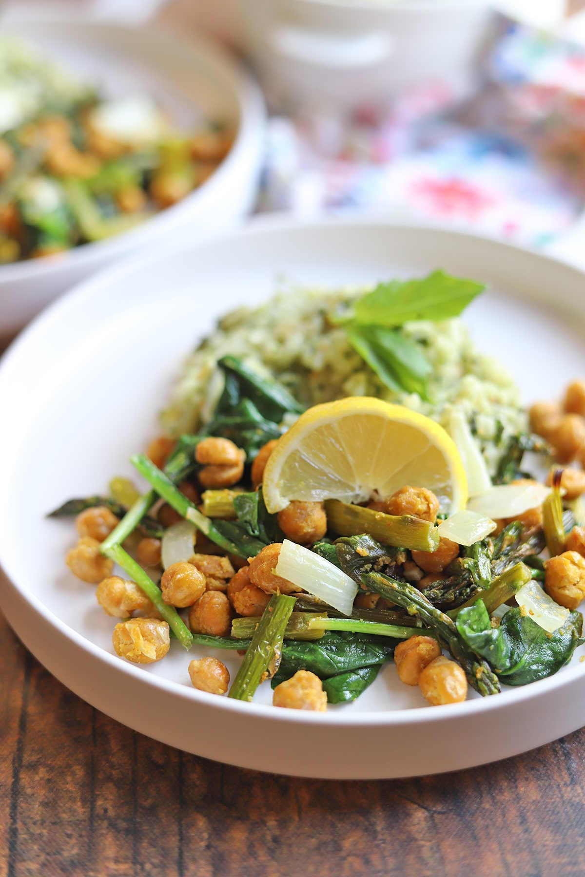 Plate with roasted asparagus, chickpeas, onions, and a lemon wedge.