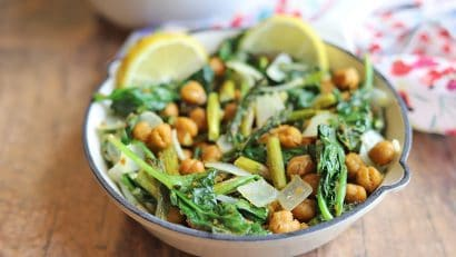 Roasted asparagus recipe in skillet with lemon slices, spinach, and chickpeas.