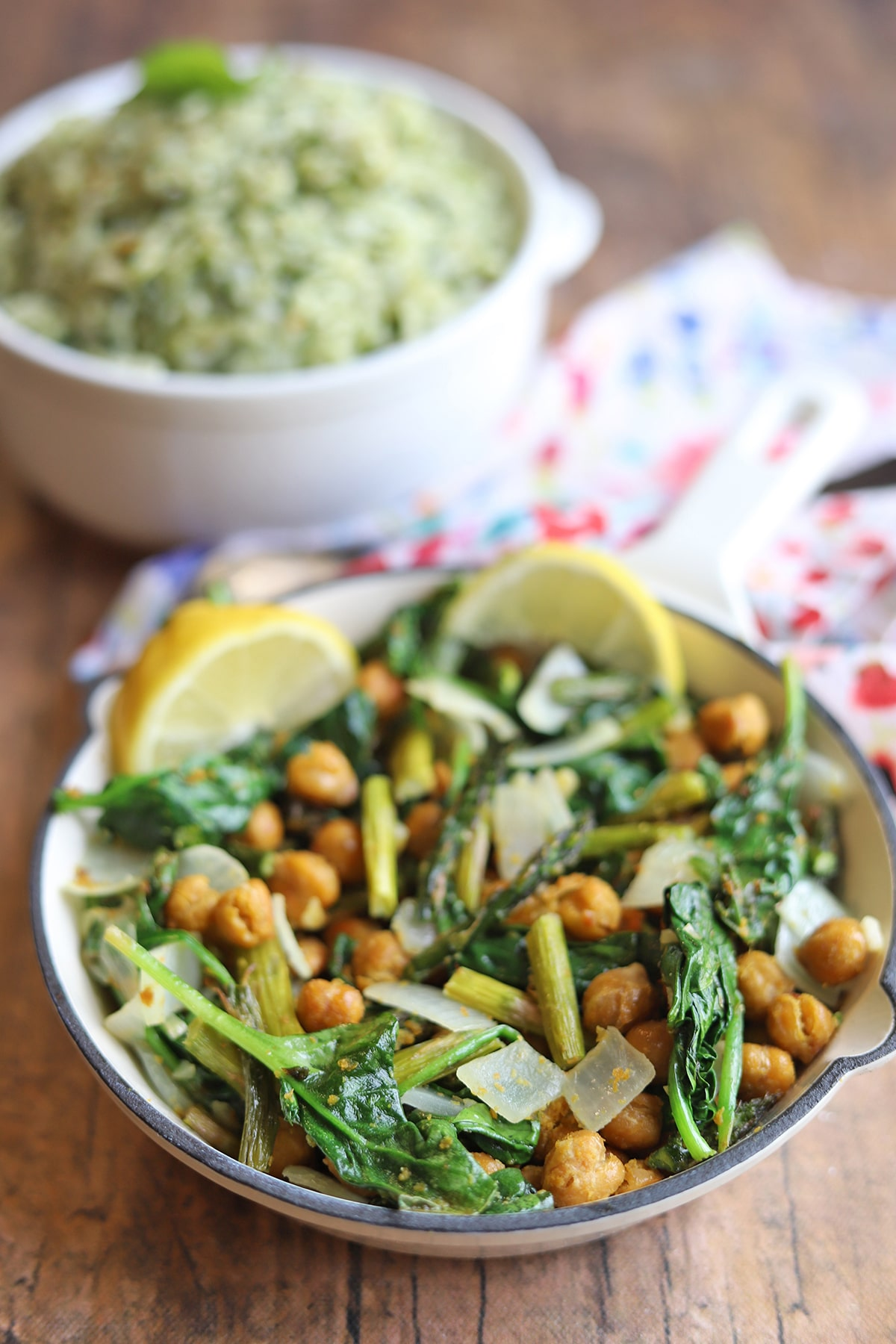 Roasted asparagus in skillet with chickpeas and spinach. Pesto rice on side.