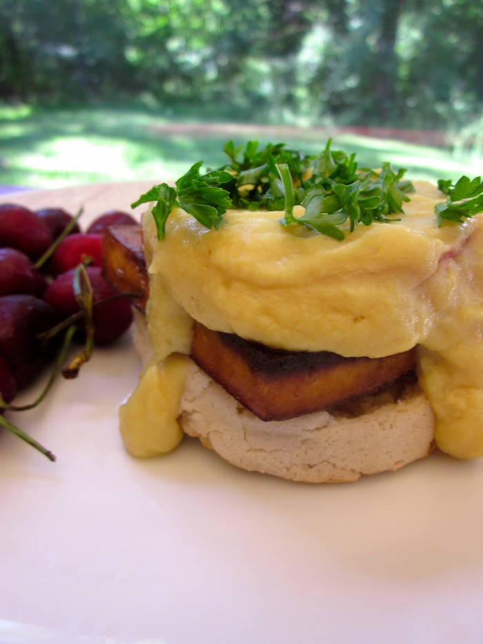 Tofu benedict with cauliflower-based hollandaise on plate with cherries.