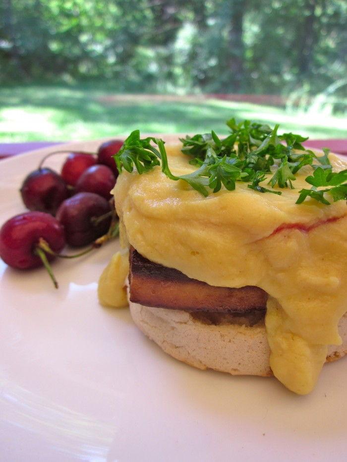 Vegan eggs benedict with cauliflower hollandaise on plate with cherries.