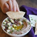 Text overlay: Olive hummus. Hand dipping pita into dip.